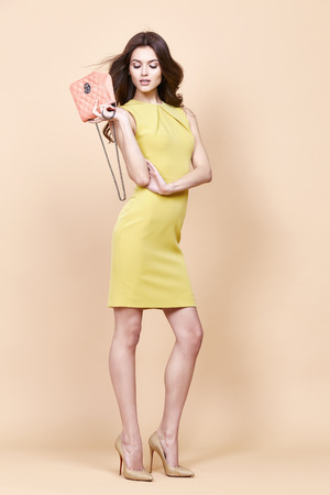 hair fashion: Glamour fashion woman long brunette curly hair natural evening makeup wear sexy short stylish yellow cotton dress from new catalog spring summer collection accessory handbag jewelry body shape care.