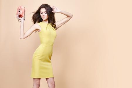 グラマー ファッション女性長いブルネットの毛自然夜化粧を着用する新しいカタログからセクシーな短いスタイリッシュな黄色いコットン ・ ドレ 写真素材