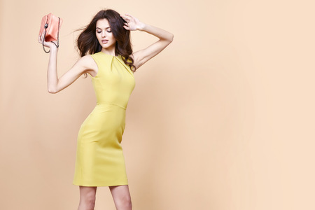 Glamour fashion woman long brunette curly hair natural evening makeup wear sexy short stylish yellow cotton dress from new catalog spring summer collection accessory handbag jewelry body shape care.