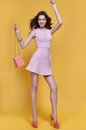 Beautiful sexy woman fashion model long dark hair beauty make up style weekend summer collection short pink dress accessory bag jewelry bracelet perfect body figure glamour clothes store party look.