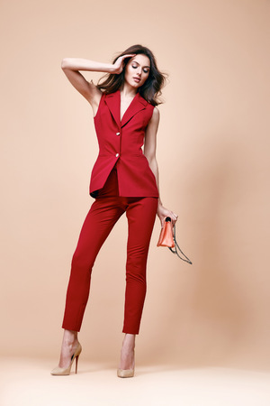 Beautiful sexy brunette woman wear red silk costume jacket and pants summer collection clothes for business lady casual work office style hold small lather goods bag make a pose fashion model catalog.