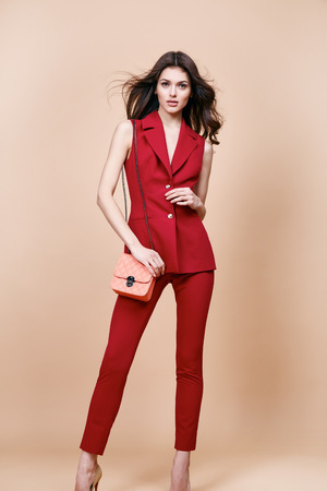 makeup fashion: Beautiful sexy brunette woman wear red silk costume jacket and pants summer collection clothes for business lady casual work office style hold small lather goods bag make a pose fashion model catalog.