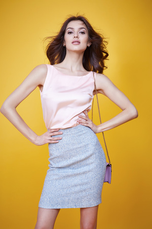 Glamour fashion style beautiful woman sexy clothes pink silk blouse cotton skirt lather trendy bag model pose catalog summer collection clothes for office businesswoman party date meeting makeup Banque d'images