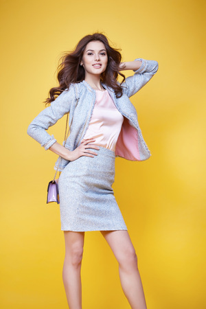 Business woman in office clothes wear costume flax jacket and skirt light blue silk pink hold hand lather bag goods accessory fashion style collection glamour pose model natural beauty makeup perfect Stockfoto