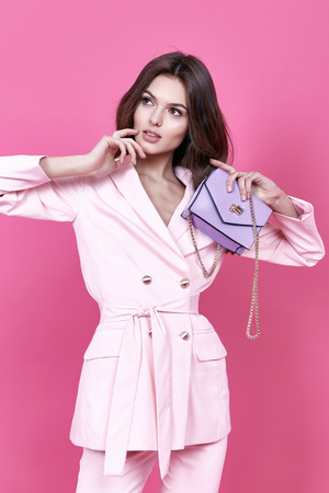 sexy pose: Beautiful sexy woman wear costume for meeting date business style pink cloak hand bag accessory fashion collection shoes model pose long brunette hair  natural make up businesswoman casual clothes. Stock Photo