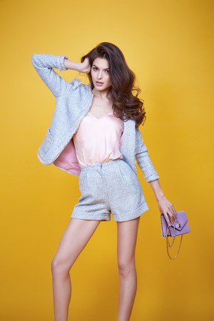 Business woman in office clothes wear costume flax jacket and shorts light blue silk pink hold hand lather bag goods accessory fashion style collection glamour pose model natural beauty makeup perfect