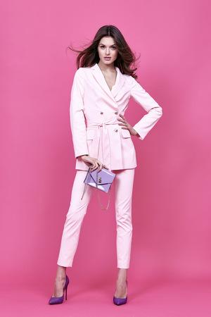 日付ビジネス スタイル ピンクのマント手を会議のための美しいセクシーな女性摩耗衣装バッグ アクセサリー ファッション コレクション靴モデル ポーズ長いブルネットの髪自然を実業家のカジュアルな服を作る。 写真素材 - 57142093