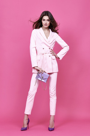 Beautiful sexy woman wear costume for meeting date business style pink cloak hand bag accessory fashion collection shoes model pose long brunette hair  natural make up businesswoman casual clothes. Imagens