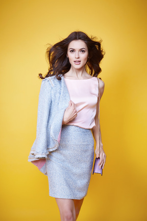 Business woman in office clothes wear costume flax jacket and skirt light blue silk pink hold hand lather bag goods accessory fashion style collection glamour pose model natural beauty makeup perfect Archivio Fotografico