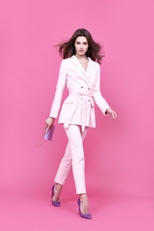 Beautiful sexy woman wear costume for meeting date business style pink cloak hand bag accessory fashion collection shoes model pose long brunette hair  natural make up businesswoman casual clothes. Archivio Fotografico