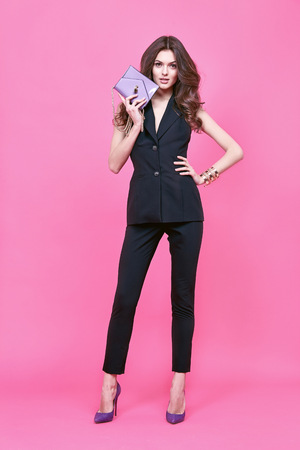 Glamour fashion style catalogue vêtements décontractés pour les femmes d'affaires rencontre date promenade fête sexy belle femme brune cheveux longs maquillage naturel usure costume de soie noire sac parfait accessoire de forme de corps.