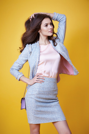 lather: Business woman in office clothes wear costume flax jacket and skirt light blue silk pink hold hand lather bag goods accessory fashion style collection glamour pose model natural beauty makeup perfect Stock Photo