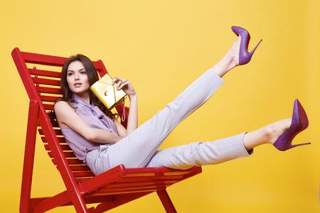 Glamour sexy vêtements de fille couleur de violence Blouse en soie avec dentelle pantalon beige en coton assis sur une chaise relax pause sac tendance de maintien des chaussures élégantes de longue brune modèle de collection de mode de cheveux beau visage pose