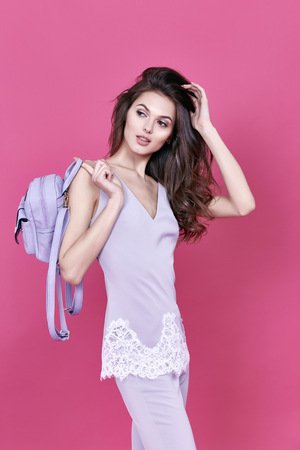 blouse sexy: Beautiful sexy woman long brunette curly hair gentle natural make up cosmetic for face care perfect body shape wear cotton pants silk blouse with lace lavender color fashion design collection hold bag
