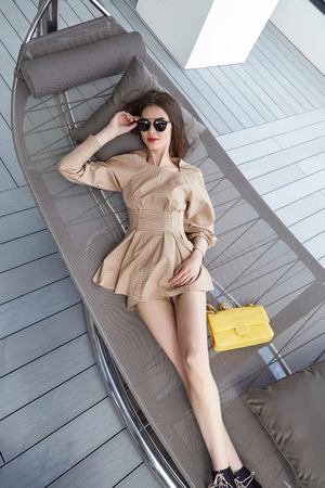 blouse sexy: Fashion model brunette hair beautiful face sexy body shape skinny tan skin style shoes luxury sunglasses bag dresses cotton blouse and shorts luxury life style catalog of clothes resort apartment. Stock Photo
