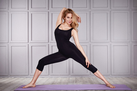 女性体操選手の美しいストレッチ体操、食事栄養、ナイロン製のフィットネス ヨガ スポーツ タイトな衣服の特別なコスチュームに身を包んだ金髪