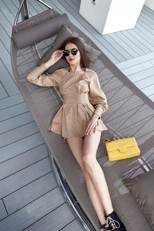 blouse sexy: Fashion model brunette hair beautiful face sexy body shape skinny tan skin style shoes luxury sunglasses bag dresses cotton blouse and shorts luxury life style catalog of clothes resort apartment Stock Photo