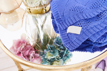silk wool: Bunch of beautiful lush fragrant hydrangea flowers stand in transparent glass vase gold plaid blanket knit from wool acrylic silk tied with satin ribbon candle mirror table comfortable interior house. Stock Photo