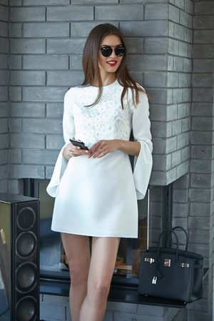Beautiful sexy woman business style casual clothes for office meeting trendy fashion dress accessory high heels shoes lather bag sunglasses party model glamour lady brunet hair phone magazine cover Standard-Bild