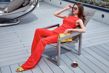 Beautiful glamour sexy woman in red silk costume with lather bag accessory trend sunglasses sit on the roof of modern building businesswoman methane or party date sun shine summer collection catalog. Standard-Bild