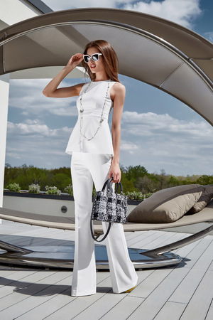 blouse sexy: Sexy glamour beautiful fashion model lady woman wear stylish costume silk blouse pants accessory bag summer collection clothes party luxury life style street look brunet hair makeup natural sunglasses. Stock Photo