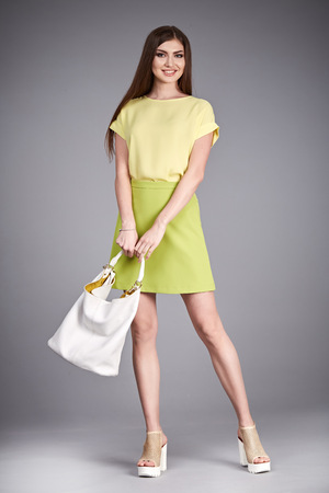 body bag: Beautiful sexy glamor woman lady long brunet hair makeup wear fashion clothes silk or cotton blouse trendy skirt lather shoes catalog in studio casual office clothes businesswoman accessory body bag. Stock Photo