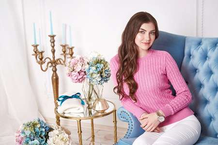 skinny jeans: Beautiful sexy woman wear pink wool merino sweater white skinny jeans perfect body shape beauty face long brunette hair interior design house room comfortable sofa restaurant flower candle accessory. Stock Photo