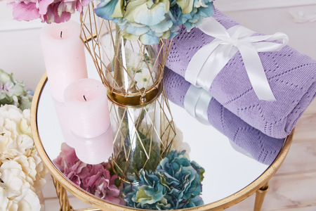bedspread: Bunch of beautiful lush fragrant hydrangea flowers stand in transparent glass vase gold plaid blanket knit from wool acrylic silk tied with satin ribbon candle mirror table comfortable interior house. Stock Photo