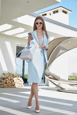 Beautiful sexy woman business style casual clothes for office meeting trendy fashion dress accessory high heels shoes lather bag sunglasses party model glamour lady brunet hair shadow magazine cover