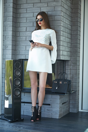 hair cover: Beautiful sexy woman business style casual clothes for office meeting trendy fashion dress accessory high heels shoes lather bag sunglasses party model glamour lady brunet hair phone magazine cover.
