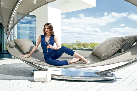 Brunette sexy woman glamour fashion luxury life style lady sit on stylish hammock modern interior building house party time drink champagne accessory lather bag summer blue sky nature resort success. Banque d'images
