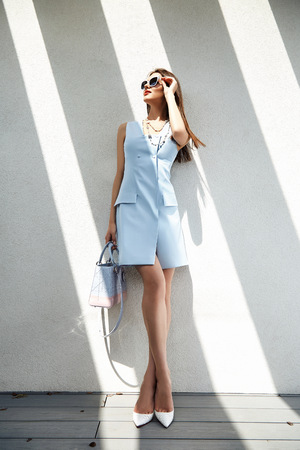 Beautiful sexy woman business style casual clothes for office meeting trendy fashion dress accessory high heels shoes lather bag sunglasses party model glamour lady brunet hair shadow magazine cower.