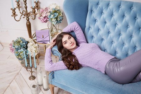skinny jeans: Beautiful sexy woman wear wool merino sweater white skinny jeans perfect body shape beauty face long brunette hair interior design house room comfortable sofa restaurant flower candle accessory
