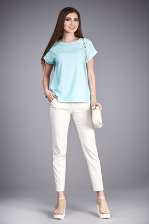 Beauty sexy woman wear stylish casual clothing for meeting walk silk blouse cotton pants high heels shoes perfect body shape fashion catalog in studio accessory long brunette hair natural make up bag. Фото со стока