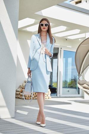 cheveux Fashion belle brune femme sexy porter des vêtements de tendance élégantes matières organiques costume lunettes de soleil style de vie de luxe sac mousse accessoire de la marque extérieure du modèle de l'heure d'été de bâtiment moderne Banque d'images