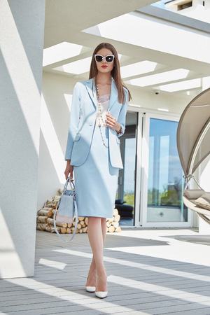Fashion beautiful woman brunette hair wear stylish trend clothes costume organic materials sunglasses luxury life style brand accessory lather bag outdoor of modern building summer time model Imagens