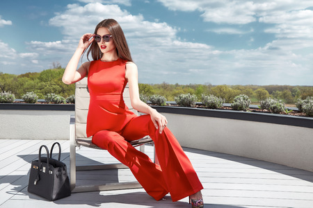 Beautiful glamour sexy woman in red silk costume with lather bag accessory trend sunglasses sit on the roof of modern building businesswoman methane or party date sun shine summer collection catalog. Stock Photo