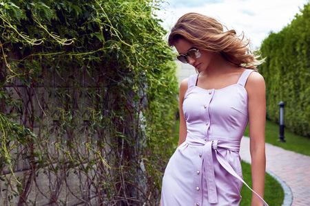 公園夏の美しいセクシーな女性散歩道緑の木々 の摩耗のスタイリッシュなショート ドレス パーティーのための天気し、グラマー ファッション服シ
