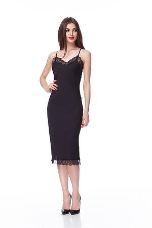 Mooie jonge sexy meisje met lang donkerbruin haar met een heldere avond make-up perfecte zomer tan dunne figuur, gekleed in zwarte zijden jurk met kant en hoge hakken schoenen zakenvrouw casual kleding