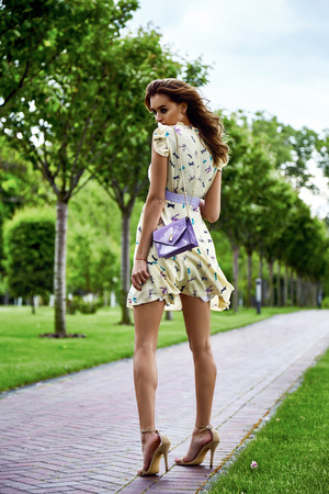 Beautiful sexy woman walk in the park summertime weather green trees road wear stylish short dress for party and walk glamour fashion clothes silk accessory bag outdoor street girl date perfect model Banco de Imagens