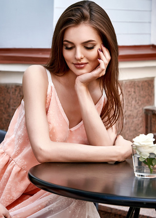 Beautiful women sit in cafe natural makeup wear pink silk dress summer outdoor date meeting brunette hair romantic flower hands face smile perfect day engage bride girlfriend