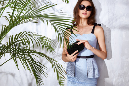 hot date: Beautiful sexy model woman wear fashion clothes stylish dress designer brandy accessory handbag jewelry party date casual collection summer mood tan skin palm shadow hot weather pose sunglasses