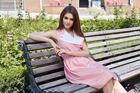 hair wind: Beautiful woman sit on the bench garden yard on the street modern city and paving the warm summer weather lady wearing a stylish dress flirting smile sweet face romantic hair wind