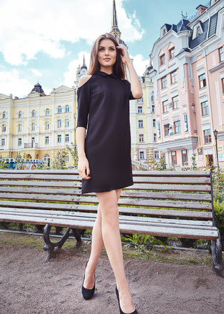 cotton dress: Sexy beautiful woman walk on the city street building bench park fashion luxury style for party date glamour pose summer clothes collection brunette hair accessory model wear black cotton dress hairdo