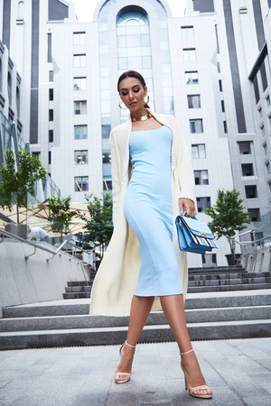 Sexy glamour woman in blue fashion style dress with handbag accessory and coat golden jewelry businesswoman walk buildings and trees street brunette wear shoes makeup lady date party meeting pose Stock Photo