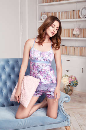 shelve: Female glamor model posing beautiful young sexy long hair brunette in silk pajamas with lace perfect figure lingerie catalog body care, cosmetics, diet, sit on the couch pillow and flower, book shelve