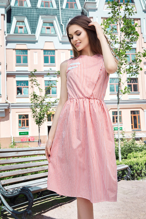 hair wind: Beautiful woman walking on the street among modern city buildings and paving the warm summer weather lady wearing a stylish dress flirting smile sweet face romantic hair wind Stock Photo