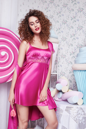 sexy lollipop: Glamor model pose beautiful stylish fashionable sexy woman brunette hair, curls, natural makeup wear pink silk pajama decoration bedroom with lots of sweets, candy, lollipop biscuit, cake, marshmallow Stock Photo