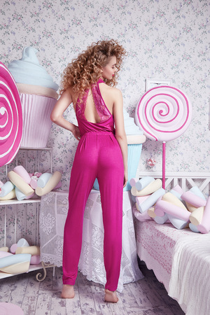 stylish hair: Beautiful stylish fashionable sexy woman wear pink pajamas blonde hair, curls, natural make-up, decoration bedroom with lots of sweets, candy, lollipop biscuit, cake, marshmallows, glamor model posing Stock Photo