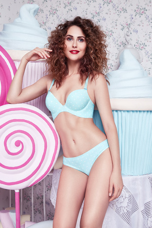 excess weight: Beautiful young sexy brunette woman with curly hair, perfect figure body, wear lingerie silk lace sweets , candy, cake biscuit, marshmallow lose excess weight, diet, proper nutrition, drainage massage